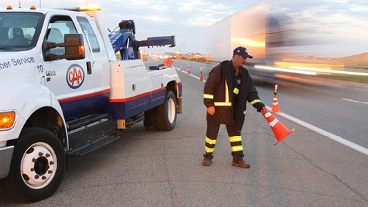 A CAA Manitoba tow truck driver placing safety cones on the road.