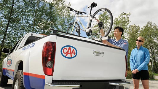 A CAA Manitoba associate repairing a bicycle on top of a CAA truck.
