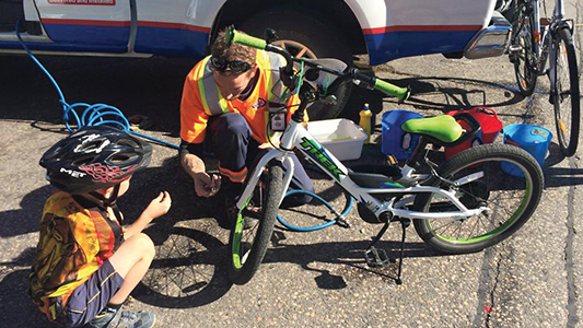 A CAA tow truck driver fixing a bicycle for a cyclist.
