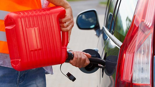 A CAA tow truck driver filling a vehicle's gas tank with gas from a gas can.