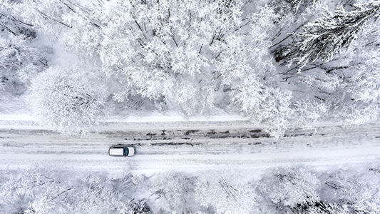 A car driving on a road in the winter time.