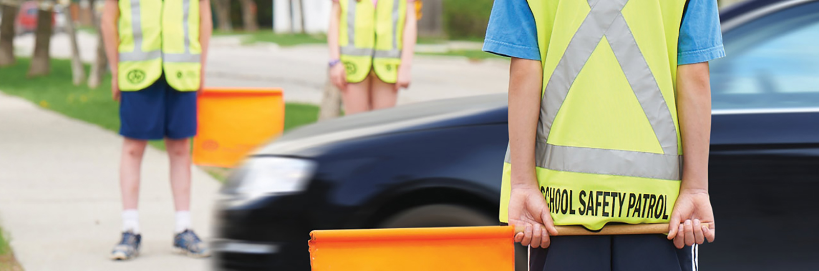 A school safety patrol wearing a yellow vest and holding an orange flag waiting for a car to cross the intersection.