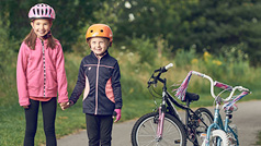Two kids wearing bicycle helmets standing beside their bicycles.