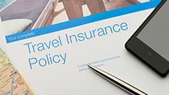 A Travel Insurance policy on a desk with a pen and mobile phone.
