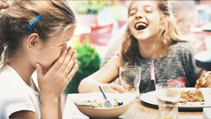 A couple of kids laughing during dinner time.