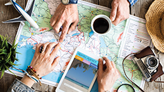 Travel planning with a map, tablet, camera and a cup of coffee.