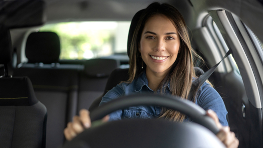 Image featuring smiling young woman leaning out drivers side window and looking to the rear, wearing mauve fedora-style hat.