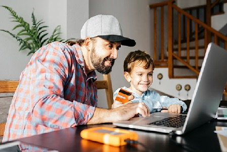 Image showing father figure with young son shopping online on laptop computer