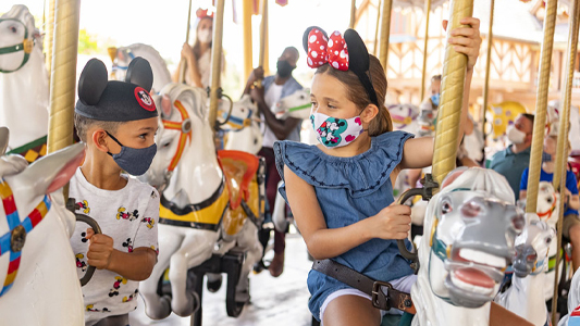 Image showing young boy and girl riding carousel horses while wearing face masks.