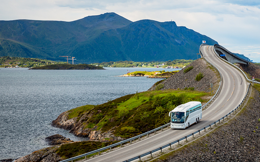 A motorcoach on a road overlooking a lake with a mountain in the background.