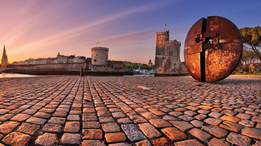 Image shows closeup of cobblestone town square with ancient castle in the background lit by a setting sun.