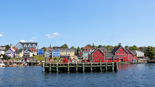 Image shows docks of small fishing village with colourfully-painted buildings in the background.