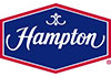 Hampton logo featuring white lettering inside a red hexigonal border with a blue background.
