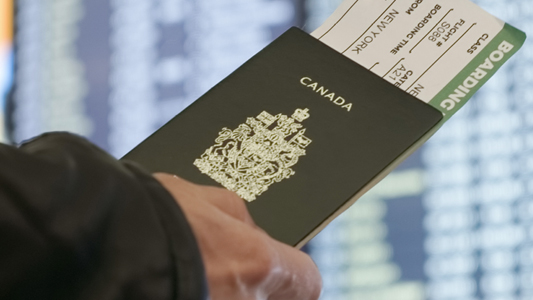 A traveller holding a Canadian passport with a flight ticket tucked inside.
