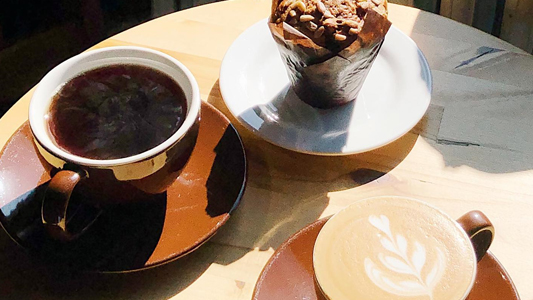 Image showing a cup of coffee and several desserts on a table.