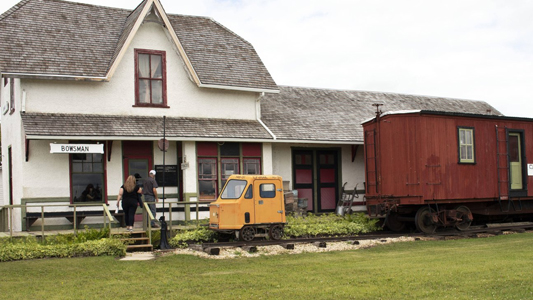 Image showing an old-style train station with a caboose and rail car in front.