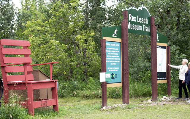 Image showing a large red wooden chair and a sign reading Rex Leach Museum Trail.