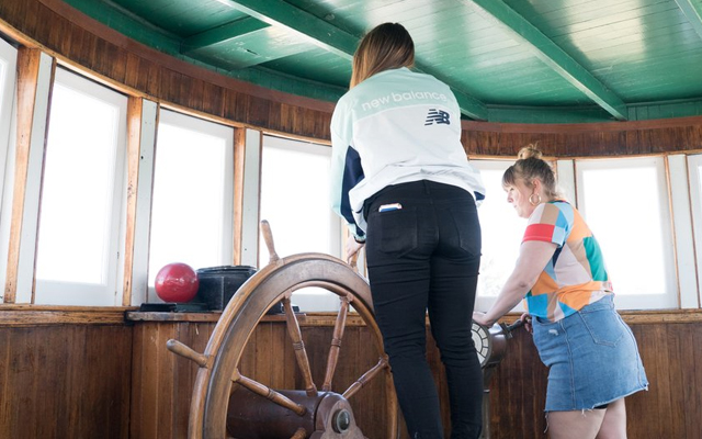 Image showing two children playing with a ships wheel inside a ship wheelhouse.