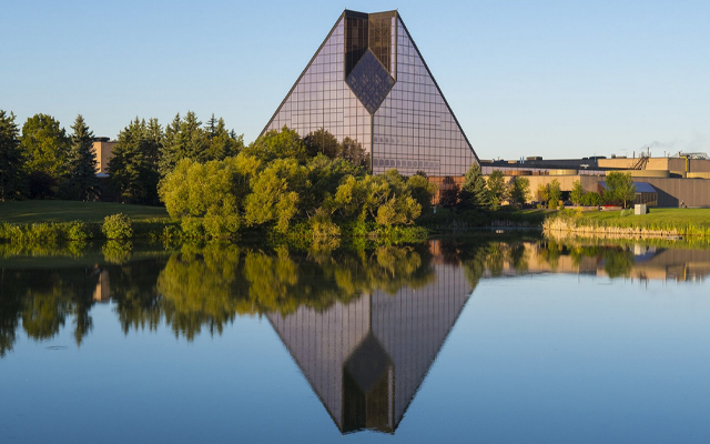 Image showing a pyramid-like building being reflected in a nearby pond.