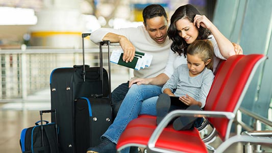 A couple with their daughter sitting on a bench waiting for their flight.