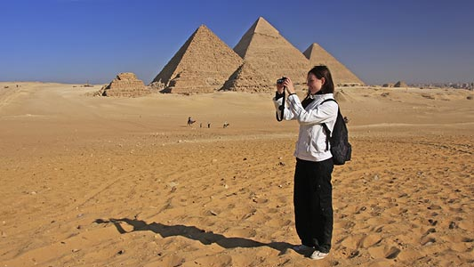 A woman standing in a desert taking a picture in front of the pyramids.